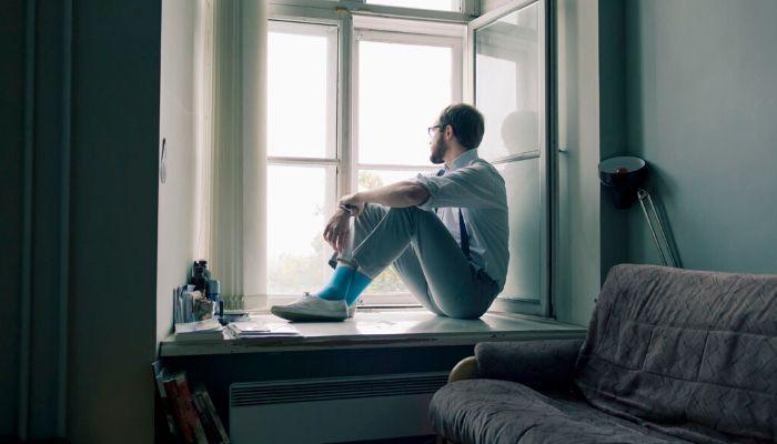 Одинокий человек мужчина сидит на окне дома